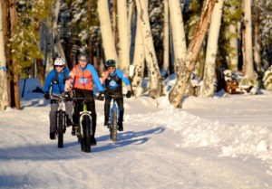three men mountain biking in snow